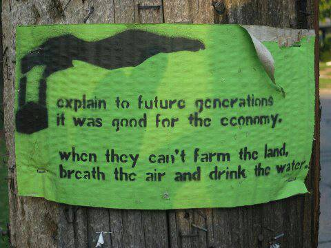"Poster that reads ""Explain to future generations it was good for the economy... when they can't farm the land, breathe the air and drink the water"""