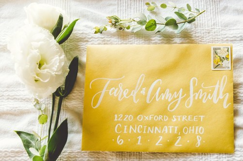 White calligraphy on a yellow envelope from Rising Tide Society Styled Shoot