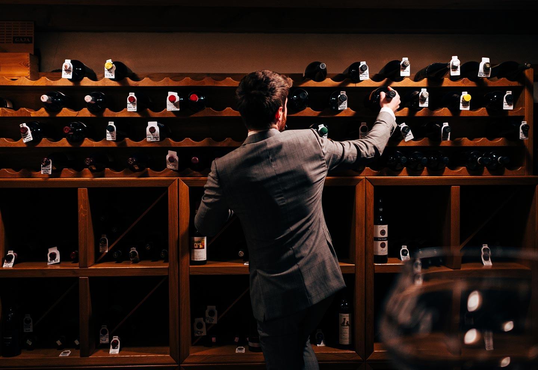 Sommelier seleziona bottiglia di vino in cantina - Ristorante stellato Gellius Oderzo