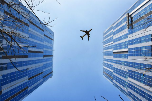 Tall buildings with aircraft flying overhead