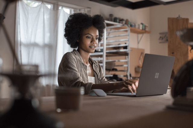 Woman working in home office on Microsoft Surface Laptop 3.