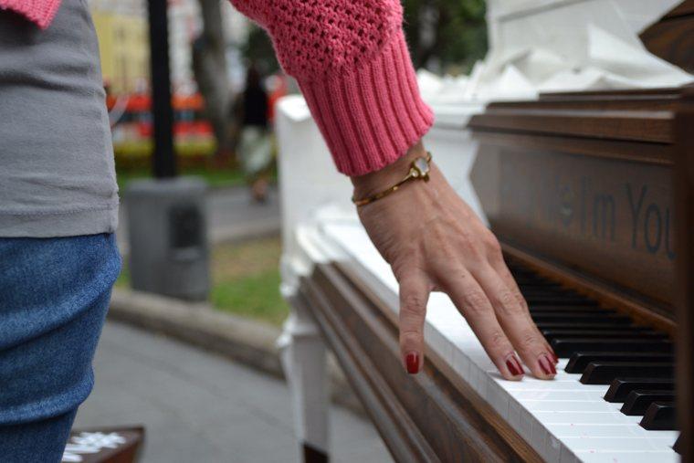 Spartiti di Mozart: la tastiera di un pianoforte e una mano che lo accarezza.