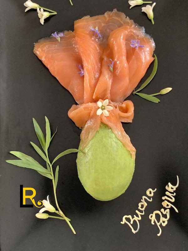 foto di uovo di Pasqua fatto con mezzo avocado e fette di salmone affumicato più la scritta Buona Pasqua con la maionese