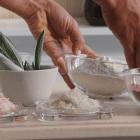 Les mains de Marion attrapent deux bols d'argile blanche et de poudre de rose
