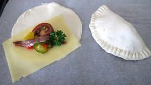 runde Blätterteigstücke werden mit der füllung belebt und zu Empanadillias zusammengeklappt
