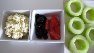 Zubereitungsschritt für die griechischen Sushi: Fetamasse, geschnittene Oliven und Tomaten. Ausgehöhlte Gurkenstücke