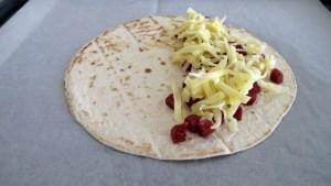 Tortilla wird mit Landjäger-Würfel und geriebenem Emmenthaler belegt