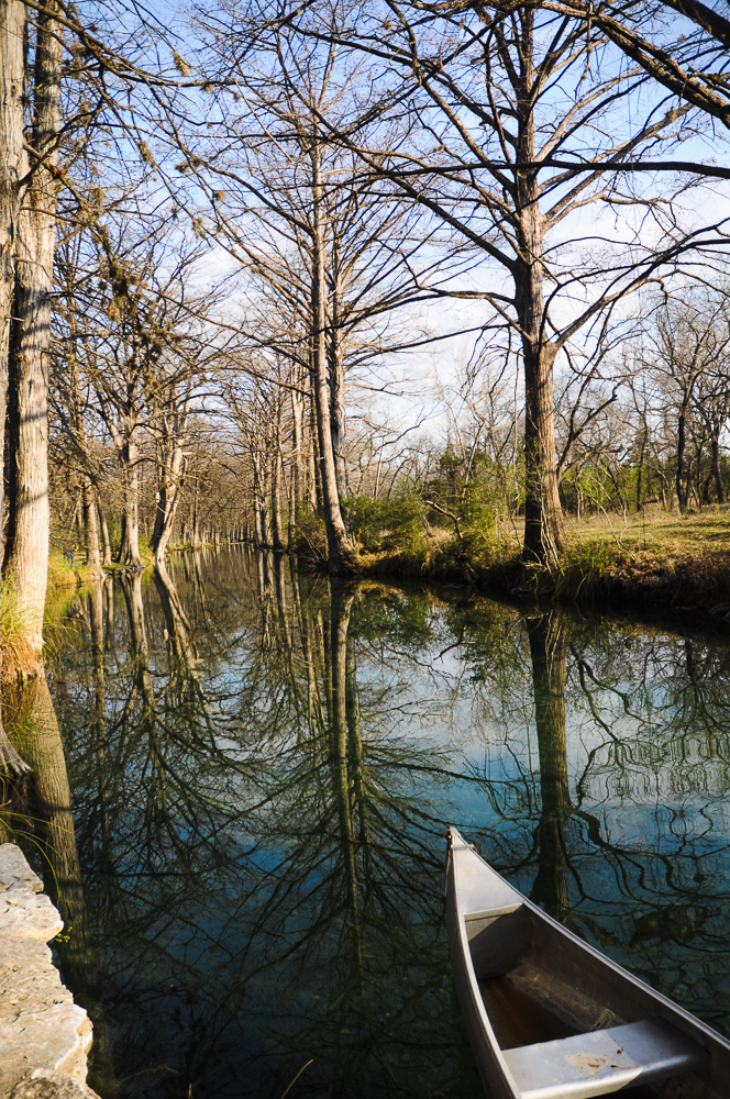 River Reflecting Trees With Canoe Wimberly, TX