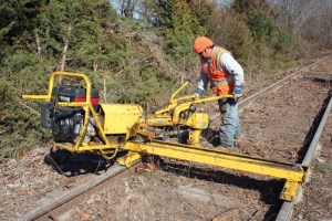 Workers use heavy equipment to dismantle the railroad tracks on the Rock Island line. The machine specifically removes the bolts and plates that hold the rails together. (Photo courtesy of Chrysa Niewald)