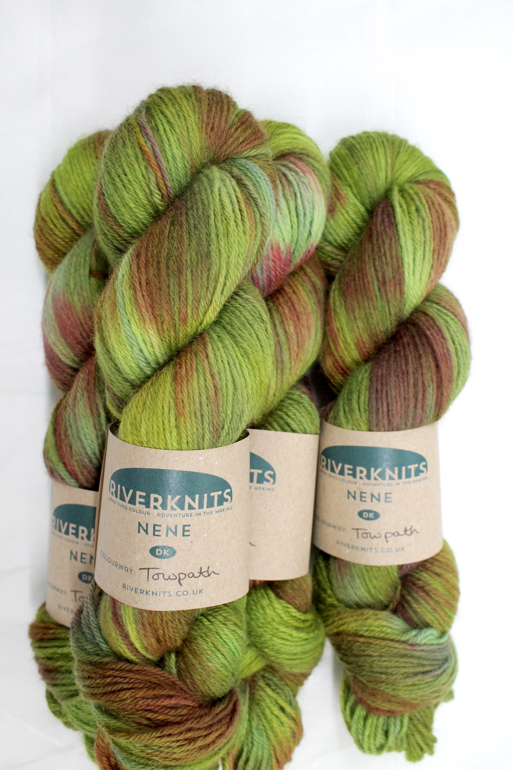Skeins dyed in variegated greens with hints of copper and red