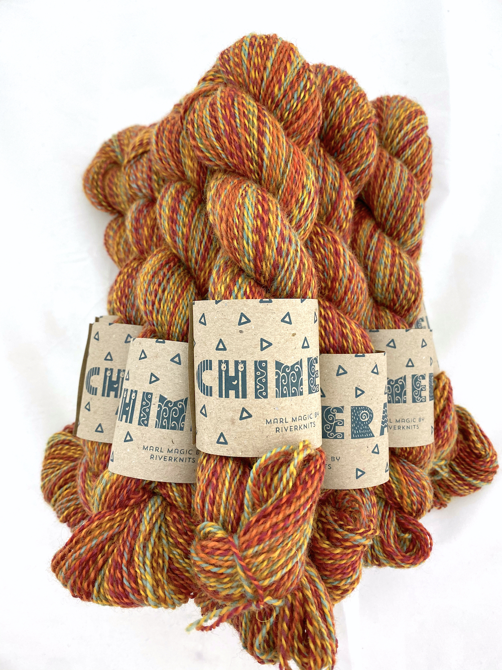 A pile of marled yarn in reds, oranges, gold, and a tiny bit of sage green.