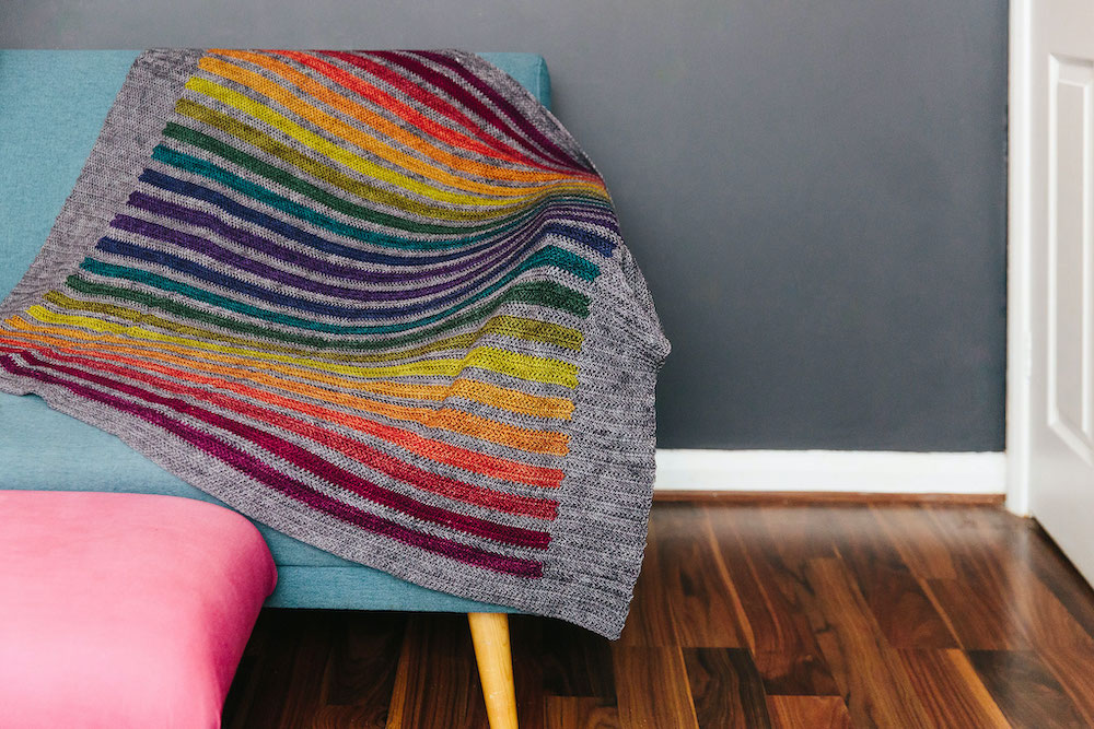 A grey crocheted blanket with rainbow stripes lays draped over a sofa.