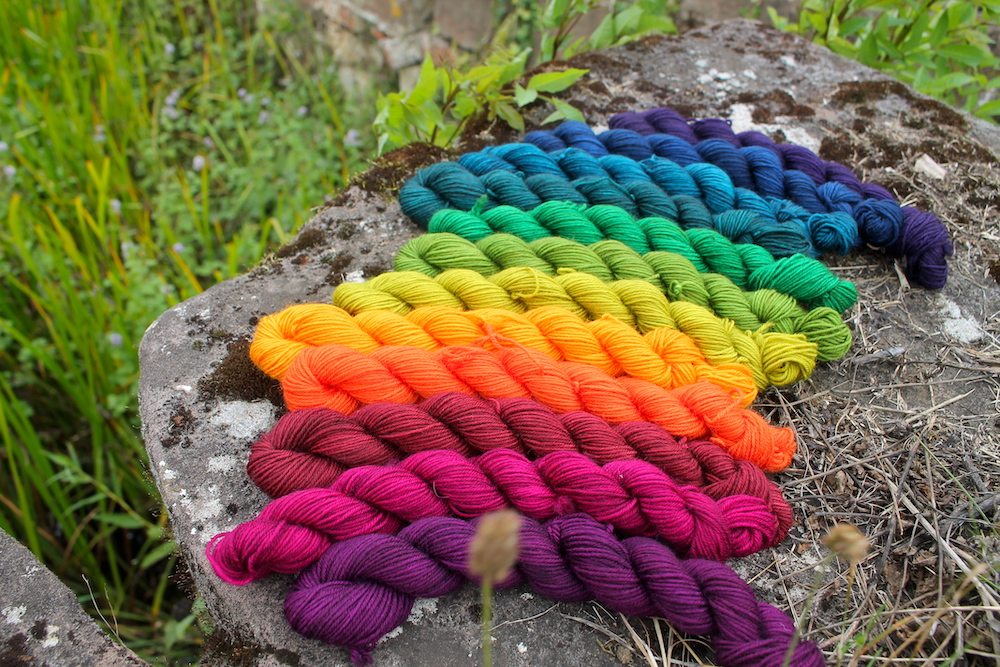 A rainbow of 12 mini skeins cycling from dark - to bright - to dark colours again