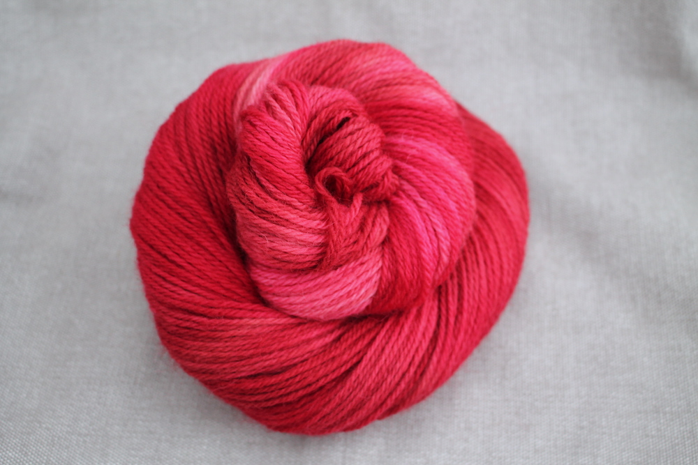 A berry red skein of Lyn DK
