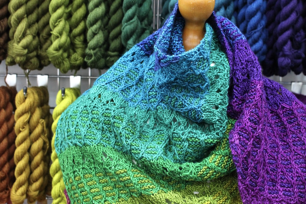 Close up of a rainbow shawl on a mannequin