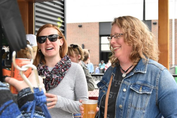 Craft beer lovers having fun at Chicken N Pickle's outdoor bar