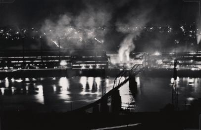 W.Eugene Smith (USA, 1918-1978). Stabilimento National Tube Company, U.S. Steel Corporation, McKeesport, e ponte ferroviario sul fiume Monongahela / National Tube Company works, U.S. Steel Corporation, McKeesport, and Union Railroad Bridge over the Monongahela River, 1955-1957 (stampa ai sali d'argento / gelatin silver print / 22.86 x 34.29 cm) Carnegie Museum of Art, Pittsburgh. Gift of the Carnegie Library of Pittsburgh, Lorant Collection. © W. Eugene Smith / Magnum Photos