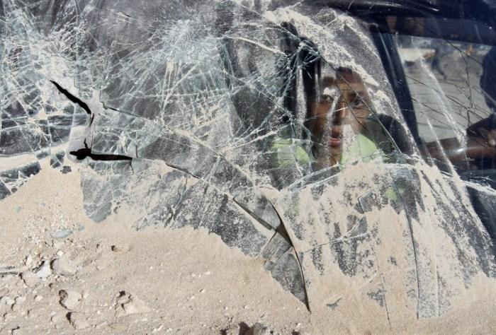 A young boy looks through broken glass a