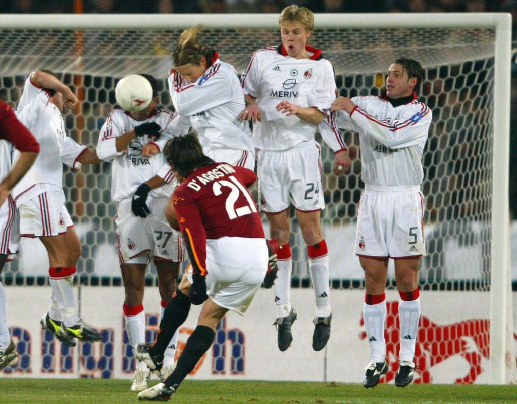 ROME, ITALY: Roma's Gaetano D'agostino (C) shoots a free kick against AC Milan's , during their italian cup quarter-final soccer match, 22 January 2004 at the Olympic stadium in Rome. AFP PHOTO/ Patrick HERTZOG (Photo credit should read PATRICK HERTZOG/AFP/Getty Images)