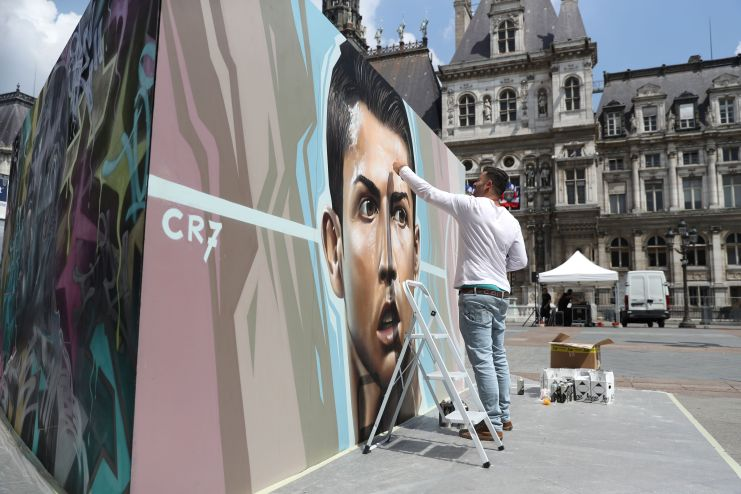 An artist paints a picture of Portugal's forward Cristiano Ronaldo for an exhibition in front of the Hotel de Ville city hall in Paris on June 7, 2016, ahead of the start of the Euro 2016 football tournament. / AFP / KENZO TRIBOUILLARD / RESTRICTED TO EDITORIAL USE - TO ILLUSTRATE THE EVENT AS SPECIFIED IN THE CAPTION (Photo credit should read KENZO TRIBOUILLARD/AFP/Getty Images)
