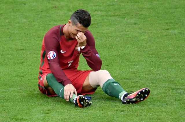 Portugal's forward Cristiano Ronaldo reacts after an injury during the Euro 2016 final football match between Portugal and France at the Stade de France in Saint-Denis, north of Paris, on July 10, 2016. / AFP / PHILIPPE LOPEZ (Photo credit should read PHILIPPE LOPEZ/AFP/Getty Images)