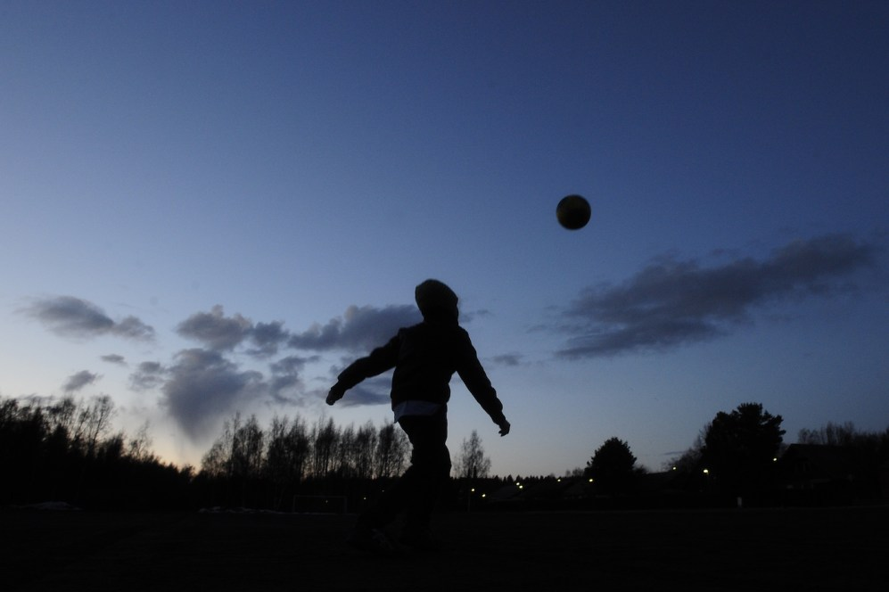 A child plays with a ball in front of a dark grey cloud with fallout, north of Vaasa at sunset, in clear skies, on April 16, 2010. Iceland's second volcano eruption in less than a month has sent plumes of ash and smoke billowing more than 20,000 feet (6,000 metres) into the sky. The massive ash cloud is gradually sweeping across Europe and forcing the continent's biggest air travel shutdown since World War II. AFP PHOTO/OLIVIER MORIN (Photo credit should read OLIVIER MORIN/AFP/Getty Images)