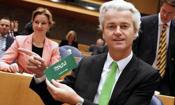 A file picture taken on December 19, 2013 shows Dutch anti-Islam and anti-immigration Party of Freedom (PVV) leader Geert Wilders gesturing and holding a sticker imitating Saudi Arabia's national flag and disparaging Islam. (AFP)