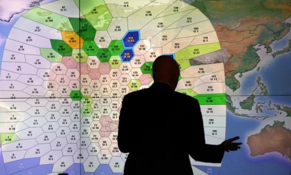 A member of staff at satellite communications company Inmarsat works in front of a screen showing subscribers using their service throughout the world, at their headquarters in London. (Reuters)