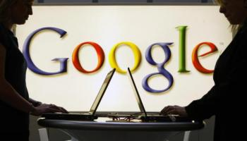 Exhibitors of the Google company work on laptop computers in front of an illuminated sign of the Google logo. (AP)