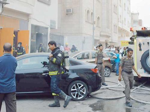 Civil Defense rescue workers prepare to enter building under fire in north Jeddah on Friday