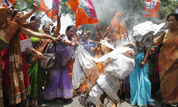 Women workers of India's ruling Bharatiya Janata Party (BJP) shout slogans and burn an effigy of Akhilesh Yadav, chief minister of the northern Indian state of Uttar Pradesh, during a protest in Allahabad on Saturday against the recent killings of two girls. (Reuters/Jitendra Prakash)