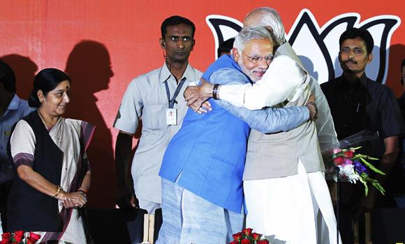 Opposition Bharatiya Janata Party (BJP) leader and India's next prime minister Narendra Modi hugs senior party leader L.K. Advani at the party headquarters in New Delhi on Saturday, May 17, 2014. India's papers are urging Modi to reach out to the nation's Muslims. (AP Photo/Altaf Qadri)
