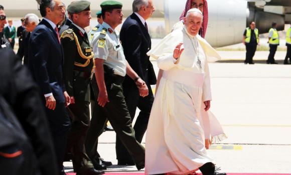 Pope Francis waves upon his arrival at Queen Alia International Airport in Amman on Saturday at the start of an intense three-day trip to the Middle East, with an appeal to members of all religions to work together for peace.
