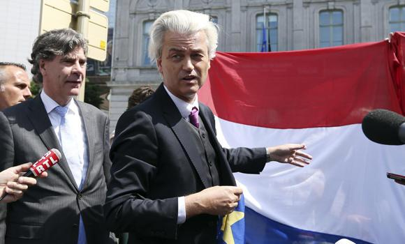 Dutch far-right Freedom Party (PVV) leader Geert Wilders speaks near a Dutch flag as he stands next to Marcel de Graaff (L), the leading PVV candidate for the European elections, during a demonstration in front of the EU Parliament in Brussels on Tuesday. (Reuters/Francois Lenoir)
