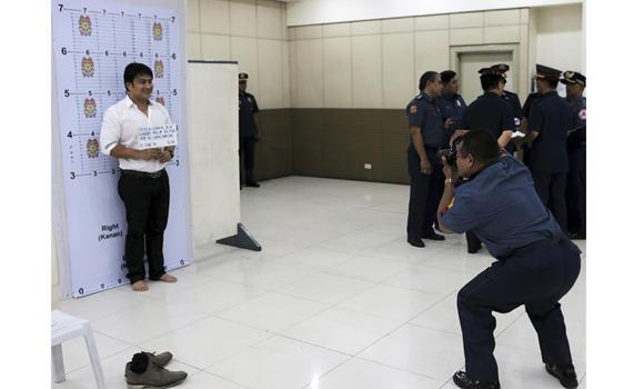 Actor-senator Ramon Revilla Jr. has his mugshot taken as part of a police booking process before he is brought to his detention cell at the national police headquarters in Quezon City on Friday.