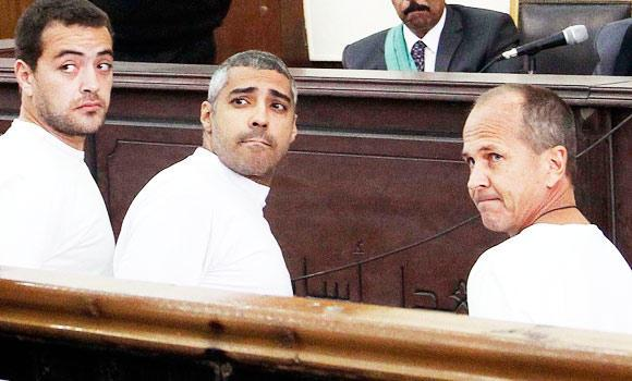 In this March 31, 2014 file photo, Al-Jazeera English producer Baher Mohamed, left, Canadian-Egyptian acting Cairo bureau chief Mohammed Fahmy, center, and correspondent Peter Greste, right, appear in court along with several other defendants during their trial on terror charges, in Cairo, Egypt.