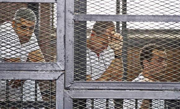 In this May 15, 2014 file photo, from left, Mohammed Fahmy, Canadian-Egyptian acting bureau chief of Al-Jazeera, Australian correspondent Peter Greste, and Egyptian producer Baher Mohamed appear in a defendant's cage along with several other defendants during their trial on terror charges at a courtroom in Cairo.