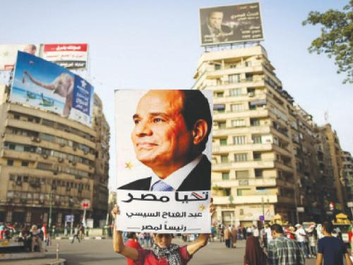 """An Egyptian man holds up a portrait of ex-army chief Abdel Fattah El-Sisi as he celebrates in Cairo's Tahrir Square after Sisi won 96.9 percent of votes in the country's presidential election. Sisi urged his countrymen to work to restore stability and achieve """"freedom"""" and """"social justice"""", in a speech after he was declared winner of last week's election. — AFP"""