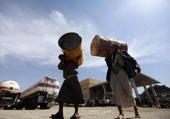 Farmers carry barrels at a fuel station during a diesel shortage in Sanaa.