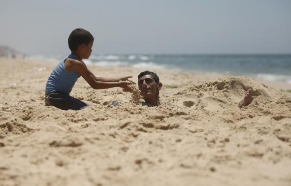 A Palestinian boy buries his brother with sand as they play on a beach in the central Gaza Strip.