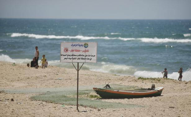 Palestinian children swim as a sign that warns against swimming is on a beach in the central Gaza Strip