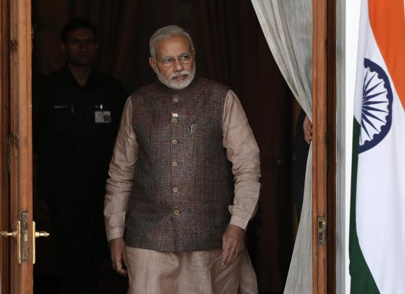 India's Prime Minister Narendra Modi comes out of a meeting room to receive his Bhutanese counterpart Tshering Tobgay before the start of their bilateral meeting in New Delhi May 27, 2014.