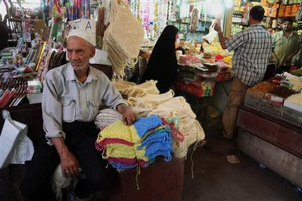 In this photo taken on June 17, 2014, people shop at a market in Baghdad, Iraq. While the Iraqi capital is not under any immediate threat of falling to the Sunni militants who have captured a wide swath of the country's north and west, battlefield setbacks and the conflict's growing sectarian slant is turning this city of 7 million into an anxiety-filled place waiting for disaster to happen.