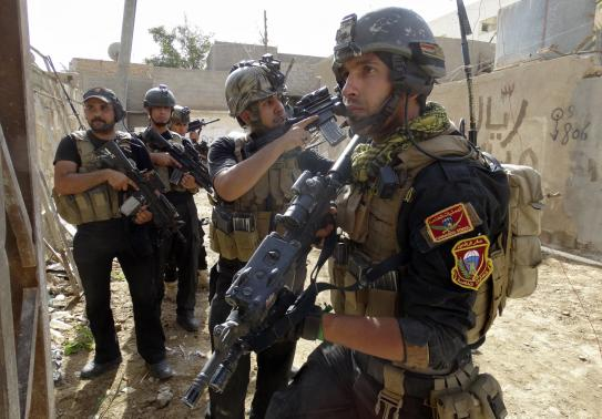 Members of the Iraqi Special Operations Forces (ISOF) take their positions during a patrol looking for militants of the Islamic State of Iraq and the Levant (ISIL), explosives and weapons in a neighbourhood in Ramadi