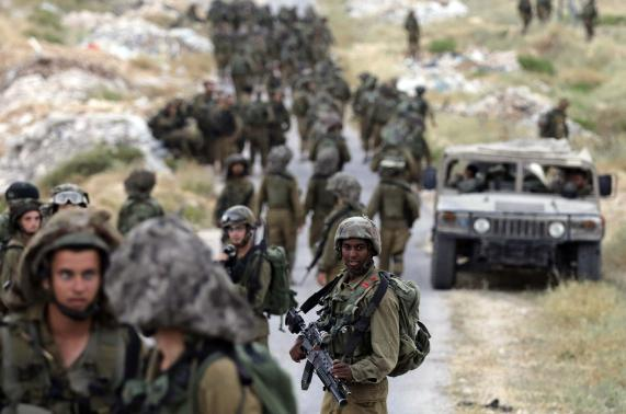 Israeli soldiers take part in an operation to locate three Israeli teens near the West Bank City of Hebron.