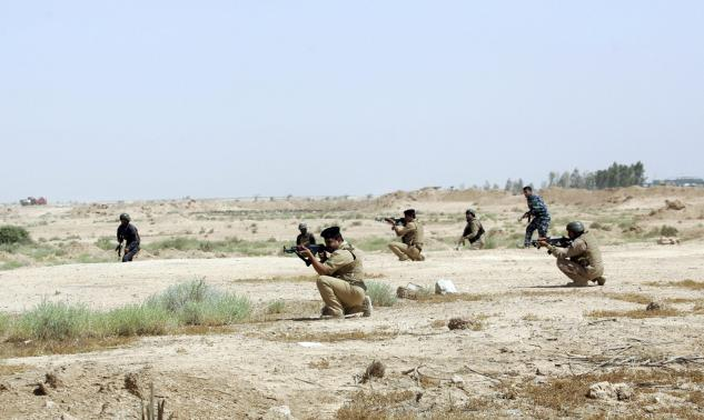 Members of Iraqi security forces take positions during a patrol looking for militants of the Islamic State of Iraq and the Levant (ISIL) west of Kerbala.
