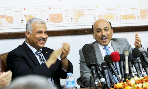 Outgoing Hamas housing Minister Yousef Jhariz, left, laughs with Mofeed Hassayna, right, the new minister in the Palestinian unity government during a handover ceremony in Gaza City, in the northern Gaza Strip, on Wednesday