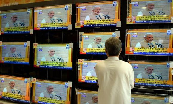 A resident watches a bank of televisions featuring images of Narendra Modi taking his oath as India's Prime Minister in New Delhi at an electronic showroom in Mumbai recently. (AFP)