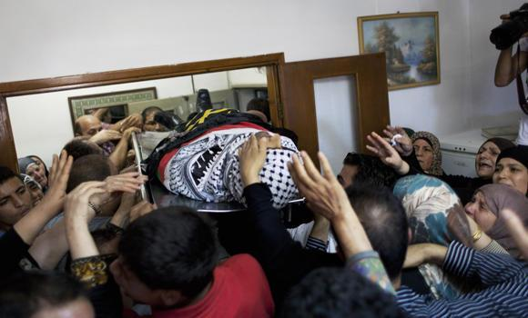 Mourners carry the body of slain Palestinian Mohammed Ismail, 31, who was shot dead after clashes separately with Israeli troops and Palestinian police on Sunday, into the family house for friends and family members to take the last look during his funeral procession at the West Bank city of Ramallah.