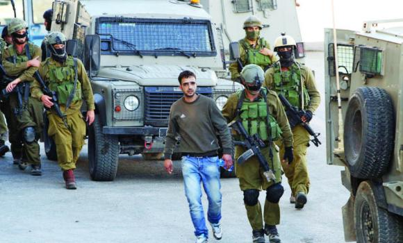 Israeli soldiers detain a Palestinian man in the West Bank town of Hebron as they search for three teenagers who went missing near a West Bank settlement.